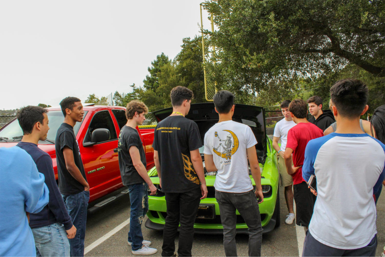 Students gather around and admire Stephen Panagiotopoulos' green Challenger Hellcat.
