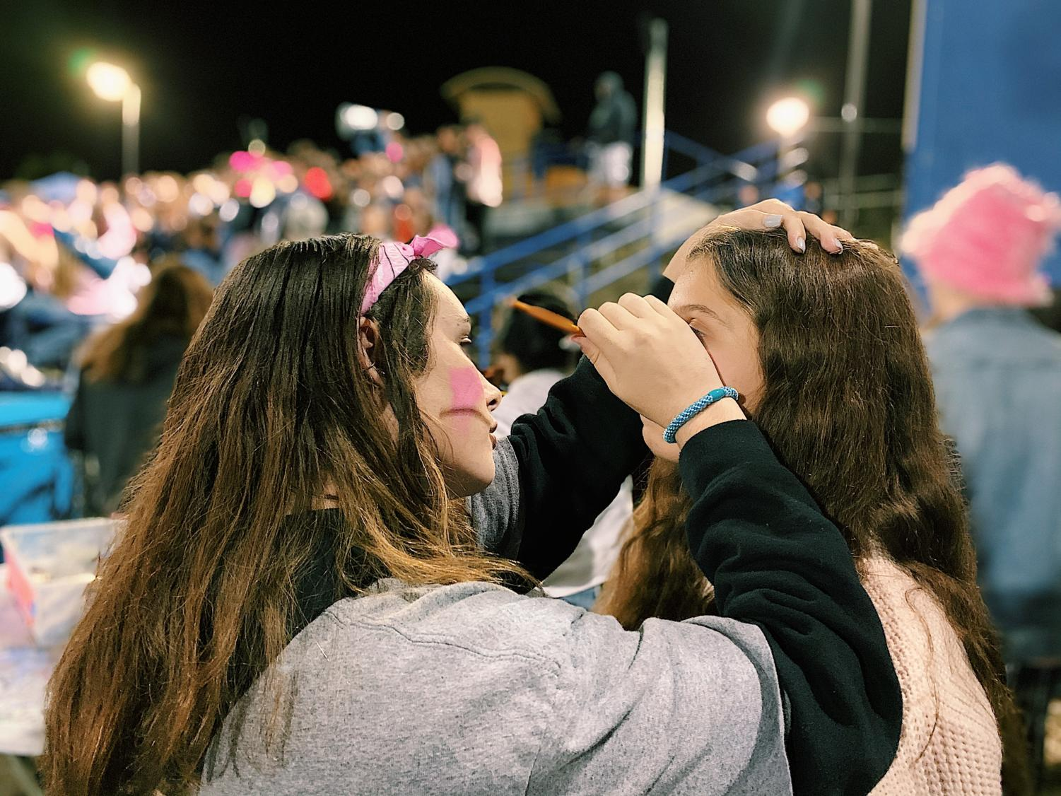 At the football game, a student gets her face painted pink in honor of Breast Cancer Awareness week.