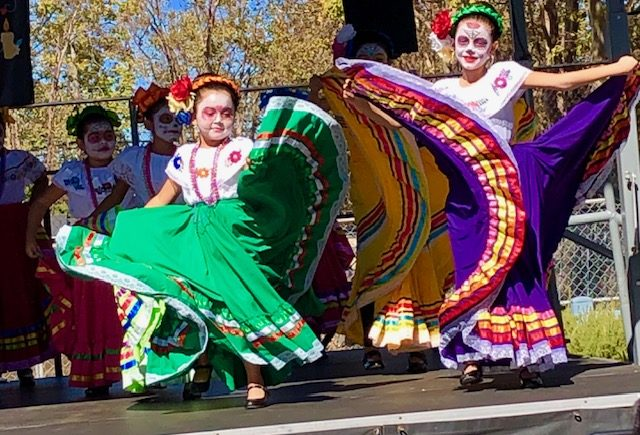 Young girls perform ballet folklorico at San Mateo's Day of the Dead Festival. Indigenous people have used dancing to pray to their ancestors and this Spanish-influenced choreography reflects Mexico's rich history.
