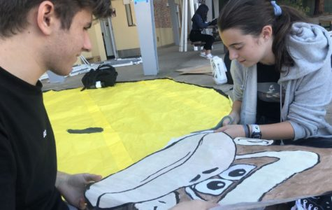 Isabella Peterson, a sophomore, and Bronsen Lasala, a sophomore, cut out a paper Donkey Kong for the sophomore float.
