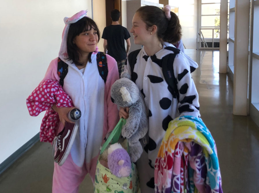Sophomore Valentina Espinosa and sophomore Marguerite Fields walk to their next class in their spirit week outfits.