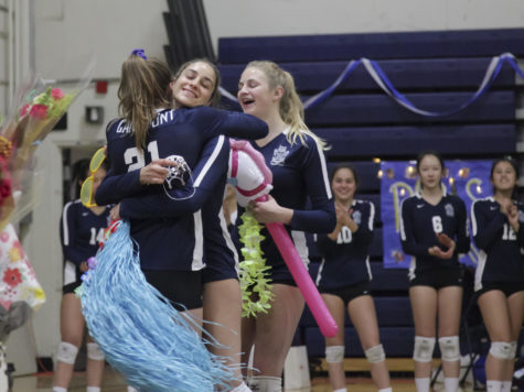 Leah McMillen, a junior, congratulates upperclassman Gaby  Pierce during Senior Night.
