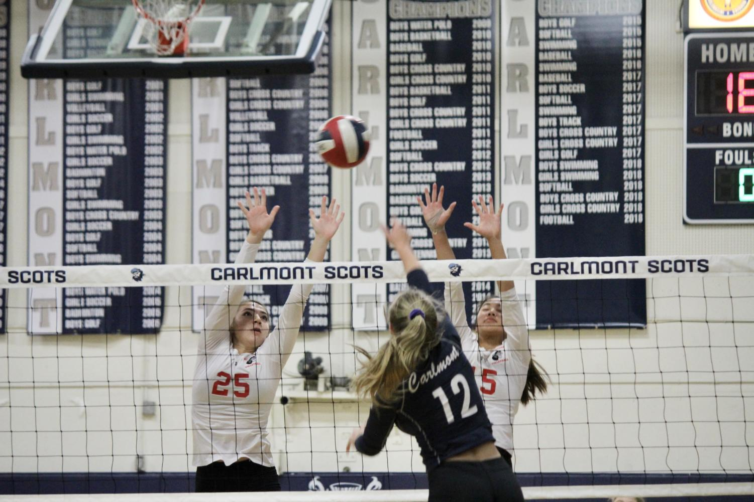 Sophomore Sasha Belov goes up to attack against two blockers.