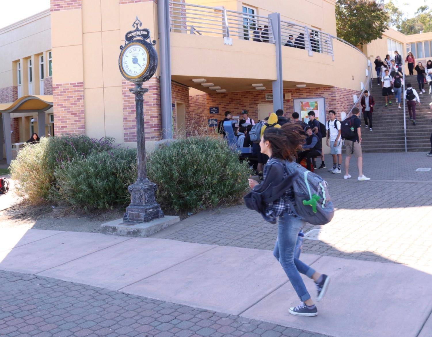 A student rushes to class as the one-minute bell rings.