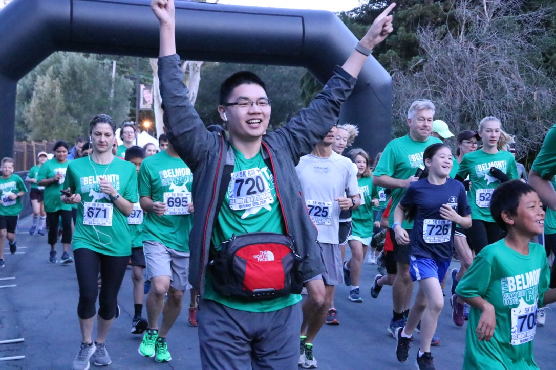 A participant excitedly raises his hands as he begins the 5K.