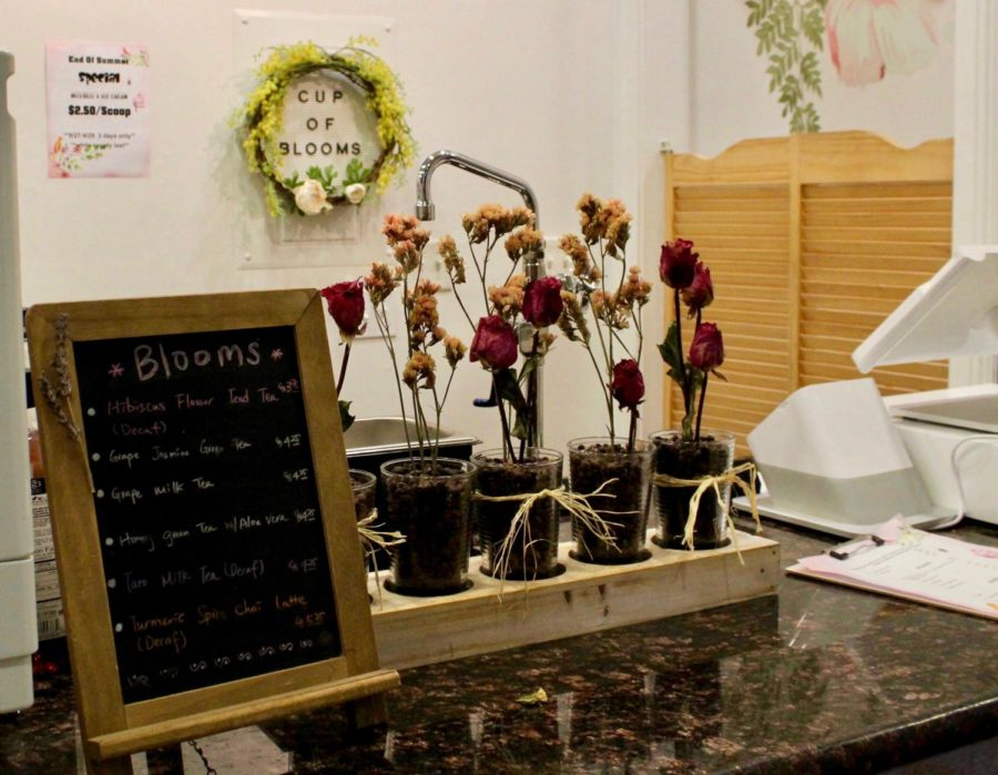 A specials menu and seasonal flowers decorate the checkout counter at  Cup of Blooms.