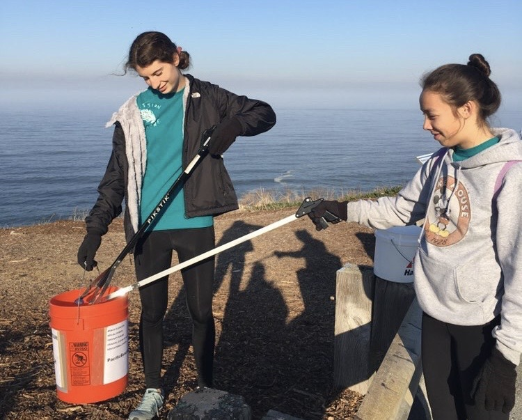 Club president Payton Zolck and club secretary Kaitlyn Fong collect trash at their beach clean up in Daly City.