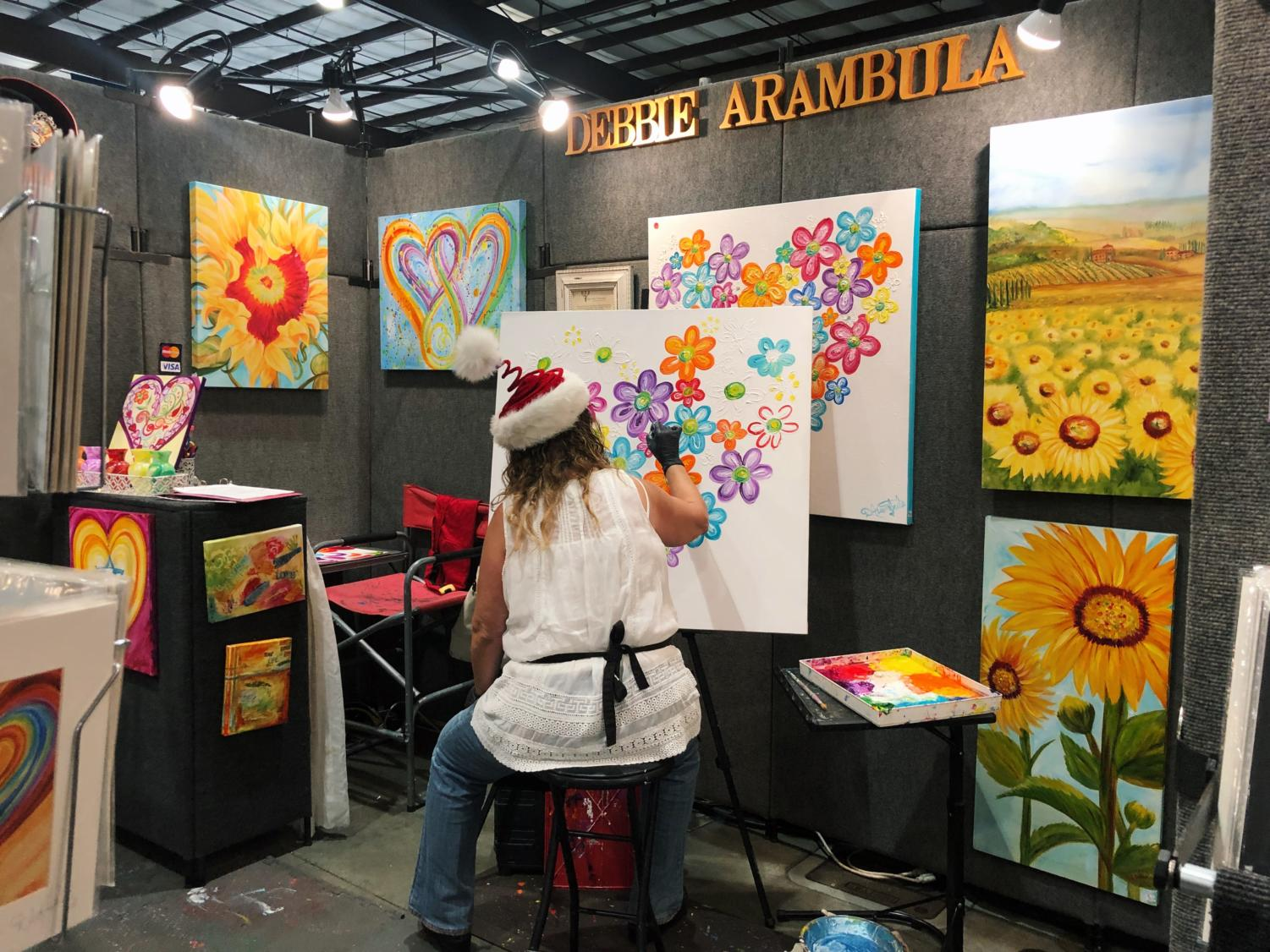 Artist and vender Debbie Arambula works to finish her painting as festival attendees walk by and observe her artwork.