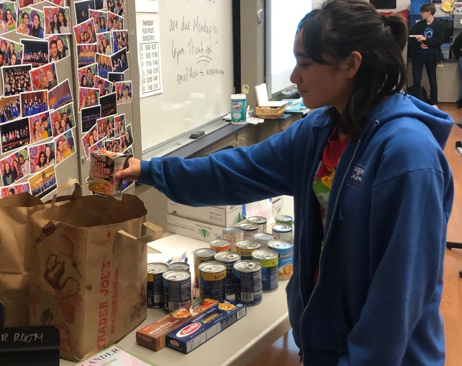 Sophomore Valentina Espinosa puts food into a paper bag for the canned food drive.