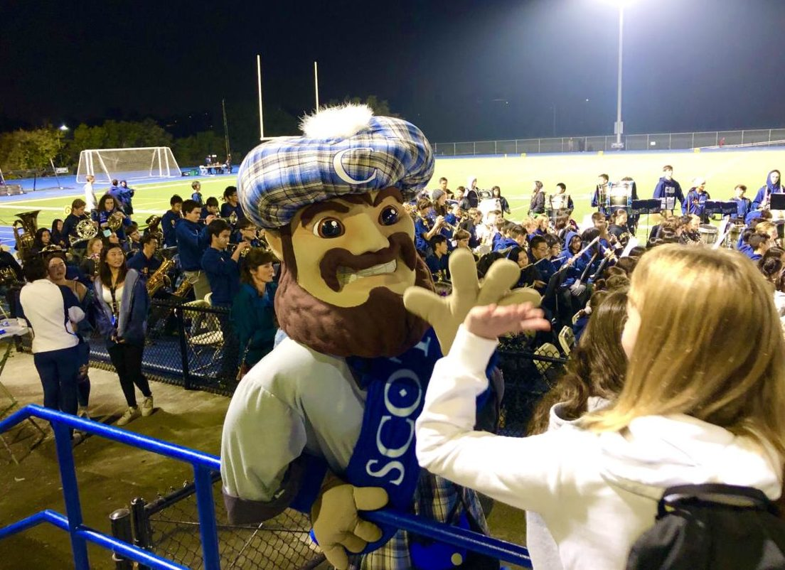 Carlmont's Mascot, Monty, gives out high fives in the football stands.