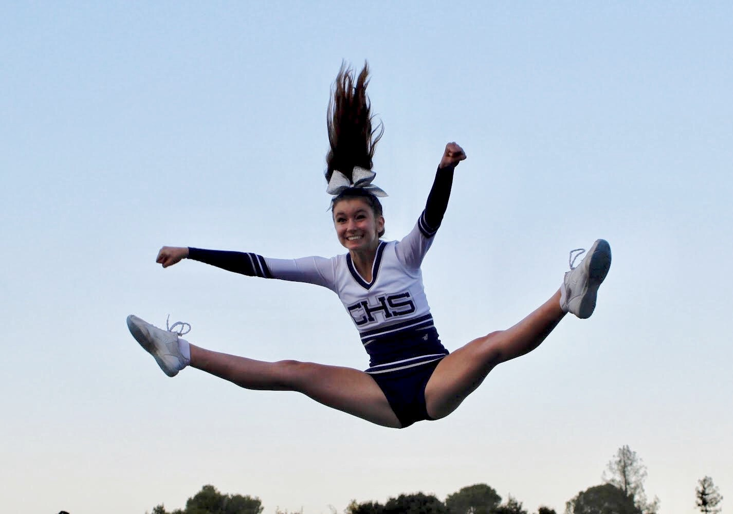 Captain Sophia Morgan, a sophomore, does a toe-touch after being thrown into the air by her teammates.