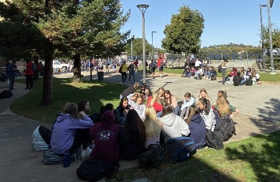 A cluster of freshman sit in the walkway of the quad, one of the most overpopulated areas during lunch.