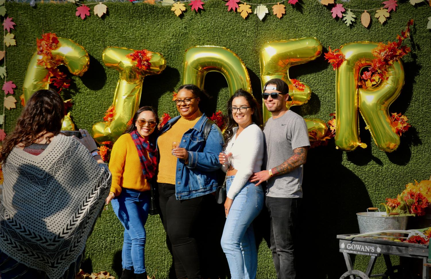 Four friends enjoy the fall-themed photo opportunity at Cider Fest.