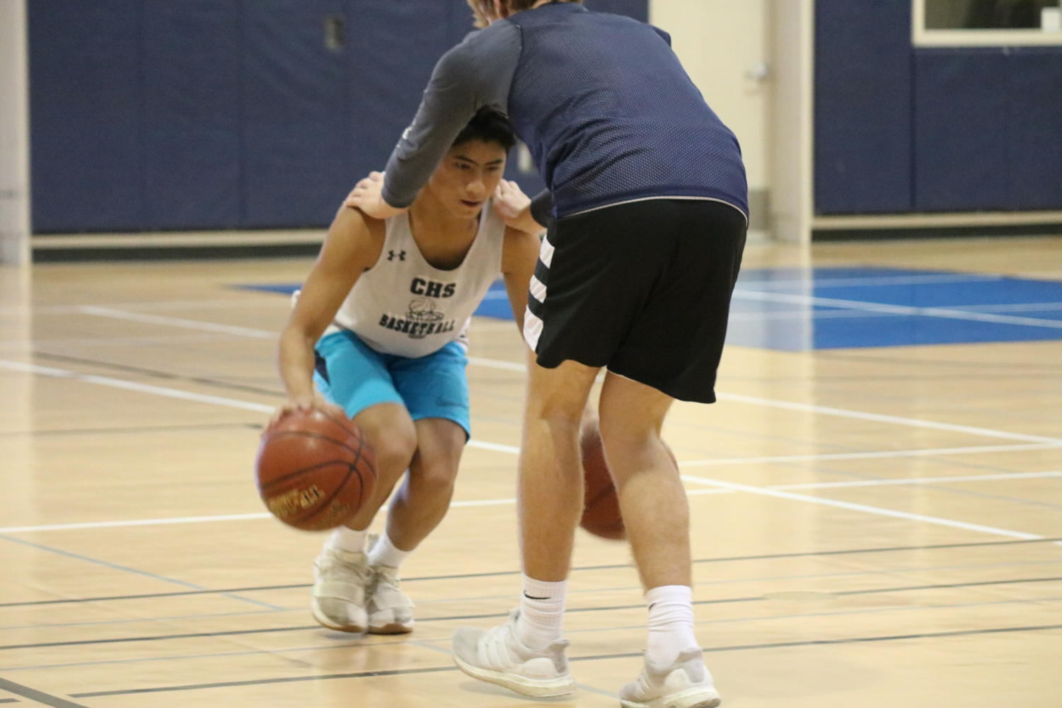 Sophomore guard Jono Sison works on his dribbling skills with freshman Trenton Corteway.