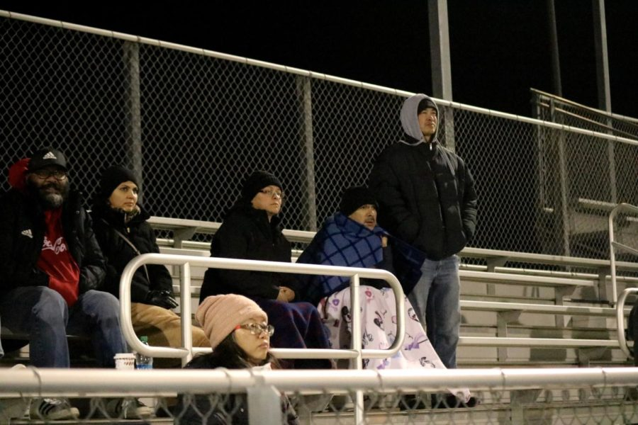 Spectators+in+the+bleachers+are+bundled+up+on+the+windy+Nov.+night+as+they+watch+the+game.