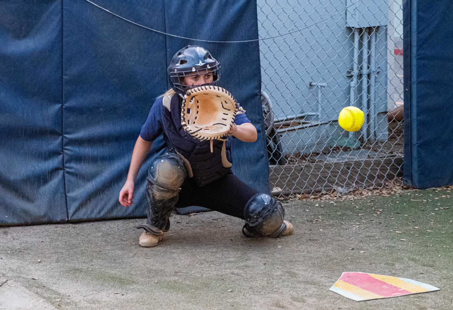 Dana Knoble, a junior, catches a ball during pitching practice.