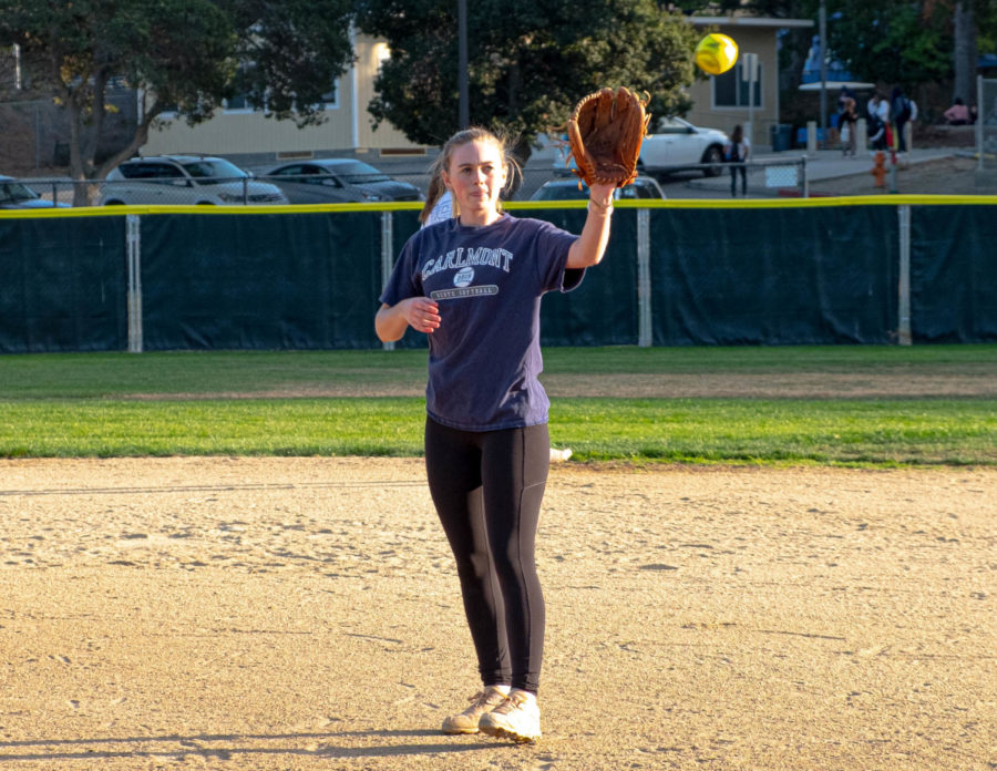 A softball player catching the ball.