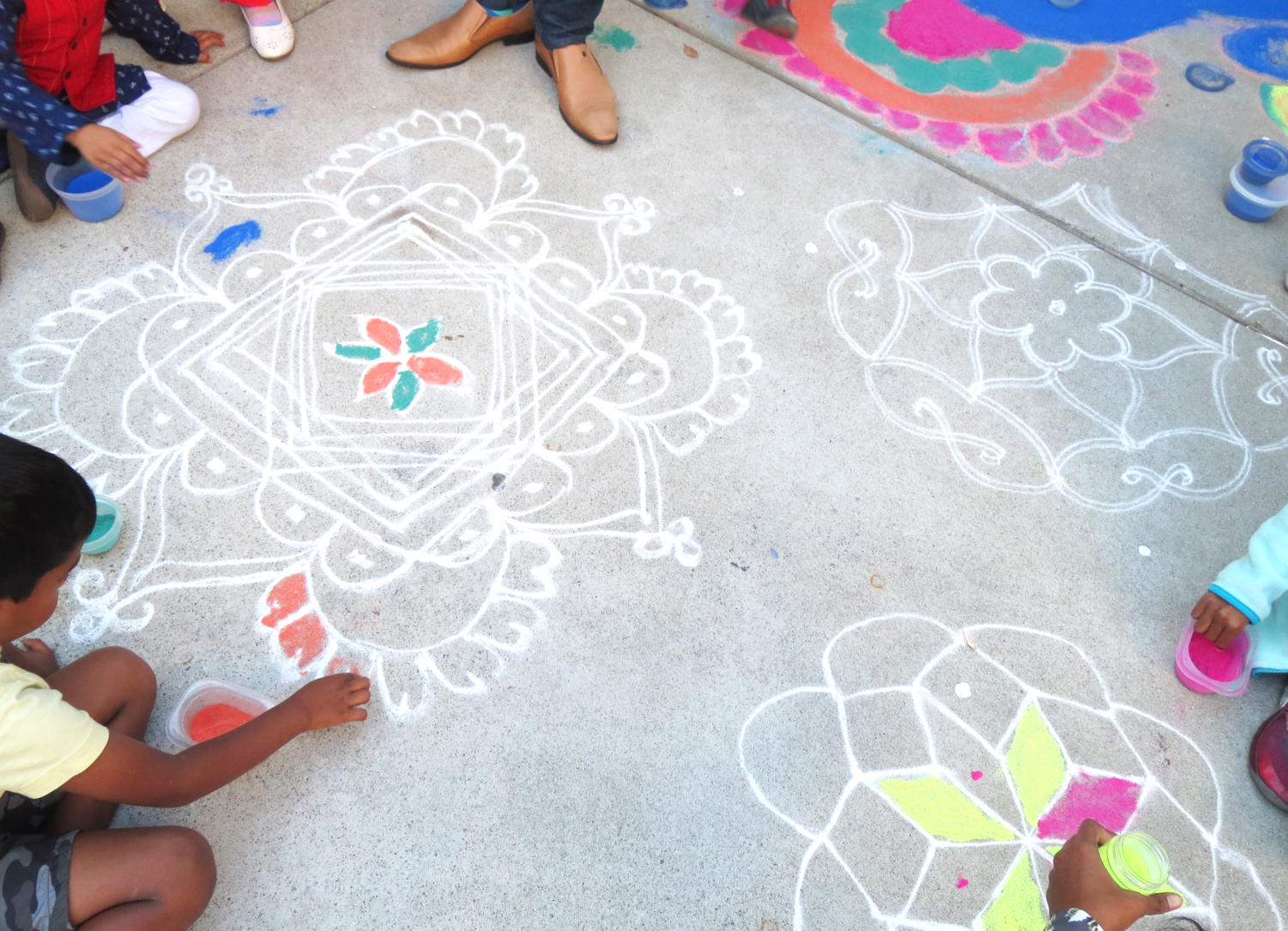 Children fill in rangoli designs with colored rice flour and sand as adults stand around eating samosas, drinking chai, and socializing.
