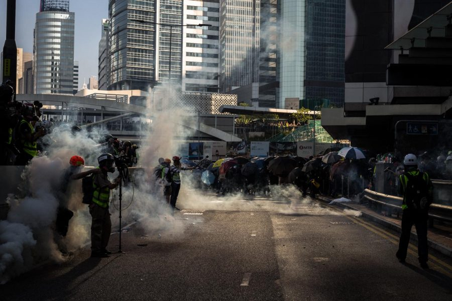 Reporters+and+protesters+in+Hong+Kong+protect+themselves+from+tear+gas+with+umbrellas+and+masks.+Protesters+use+umbrellas+in+a+variety+of+ways+in+their+ongoing+protests.
