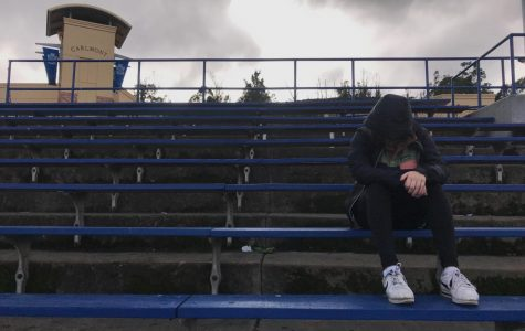 Student at Carlmont High School takes a break, and a moment to themselves, as they sit on the bleachers overlooking the field.