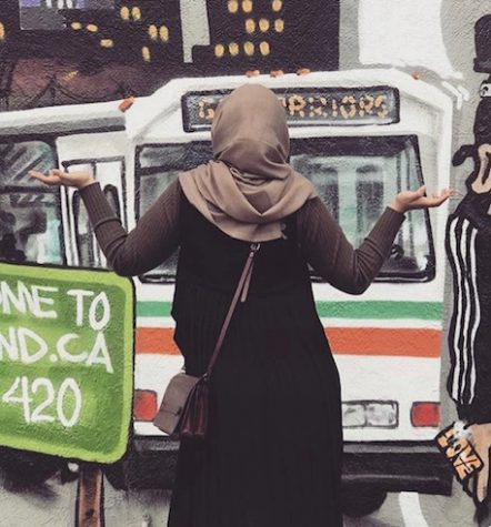 Matab Abdaljalil faces a mural in Oakland. Her headscarf and long dress in front of the marijuana reference represent the cultural mixing and differences she experienced when she first moved to the Bay Area in 2015.