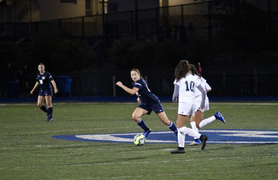 Cunningham dribbles the ball down the field as she looks for an open pass.