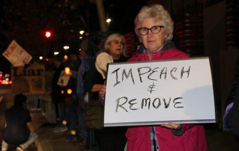 Maureen Sinnott holds a sign stating