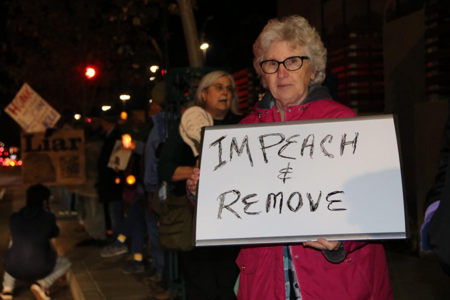 Maureen Sinnott holds a sign stating
