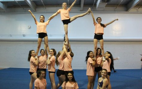 Carlmont competition cheerleaders are  warming up before practice in a complex pyramid.