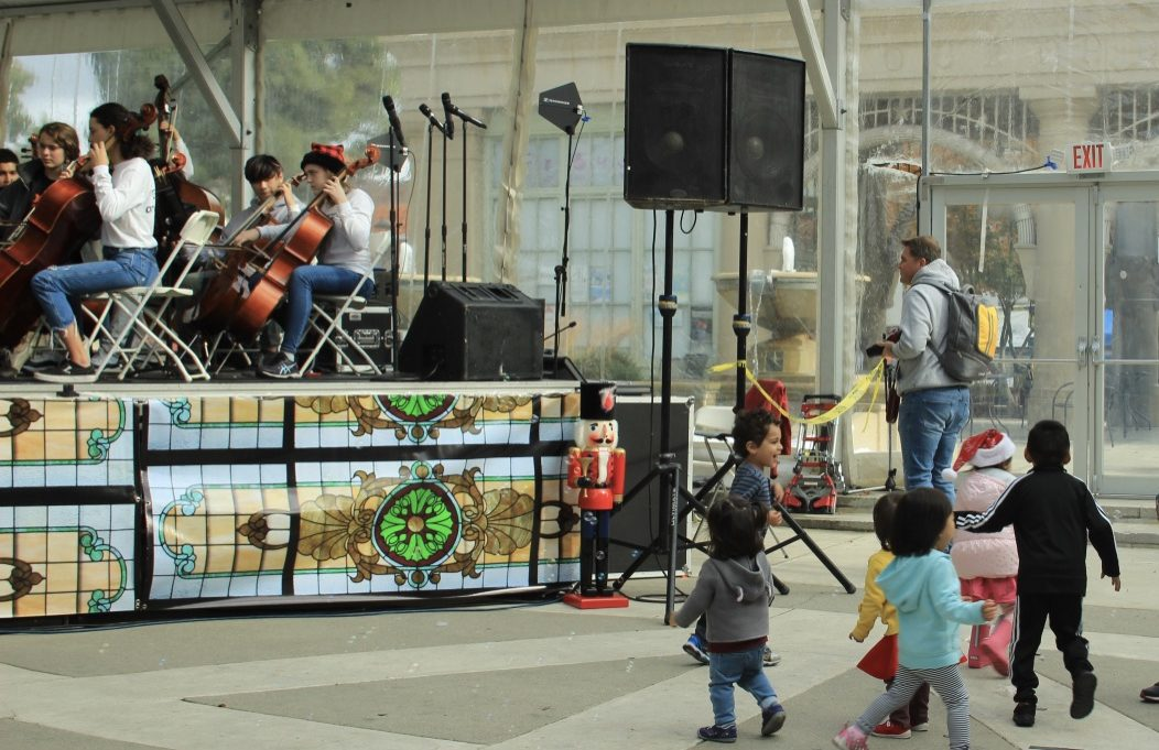 Little kids enjoy music played by the Woodside High School orchestra.
