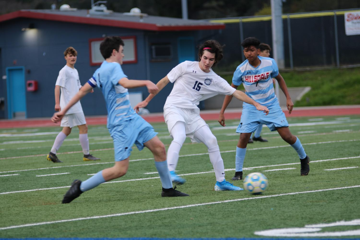 Hayden Pendleton, a sophomore, fends off Hillsdale players in order to gain control of the ball.