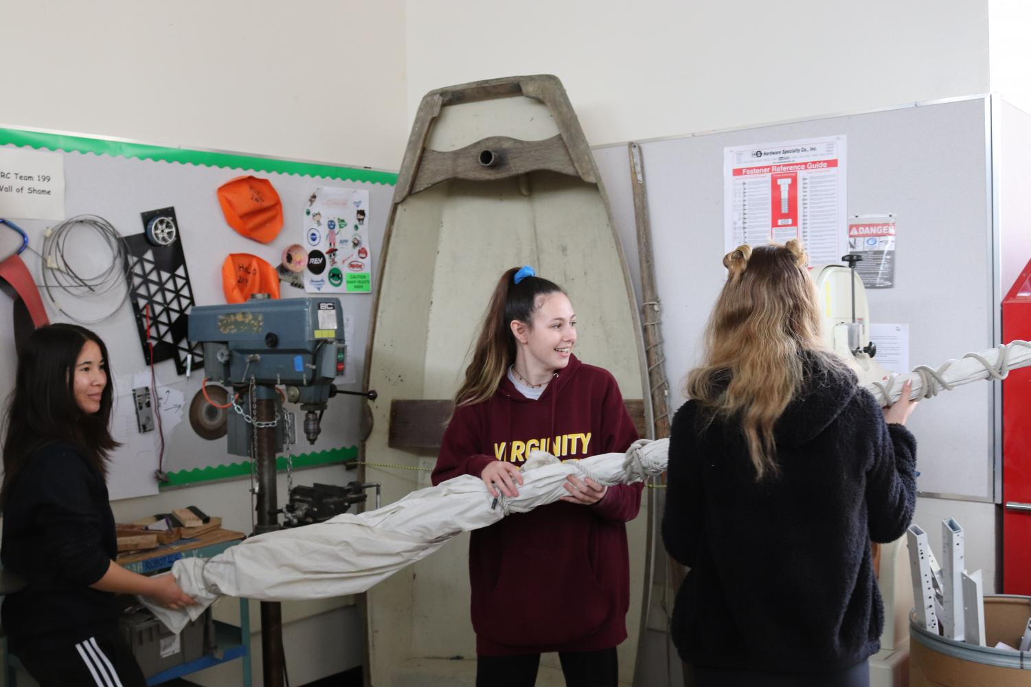 Members of Sailing Club work on improving teacher Alexander Wallace's old sail and boat, including the boom, the horizontal pole which extends from the bottom of the mast.