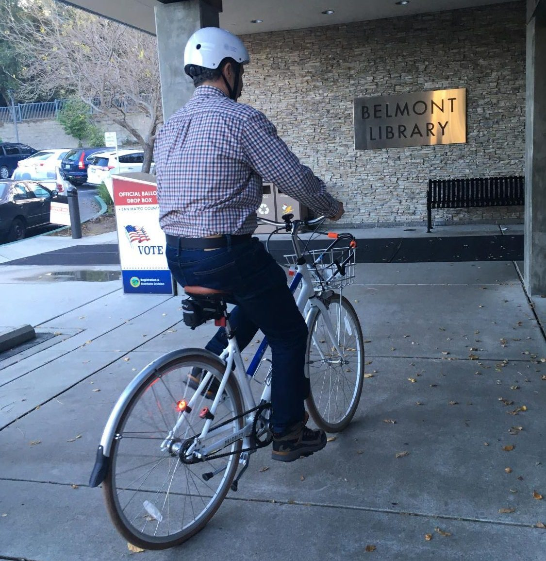 A library member rides down to the Belmont library to return his bike before closing.