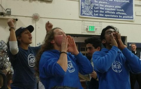The leaders of  Screamin' Scots, enthusiastically cheer after Carlmont's varsity basketball team makes a basket.