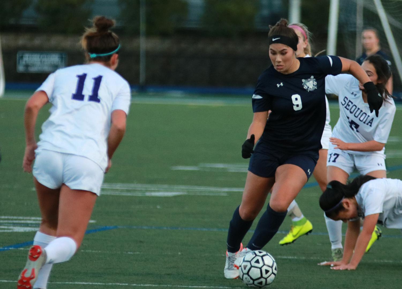 Kyla Orthbandt, a senior, dribbles the ball through Sequoia's defense.