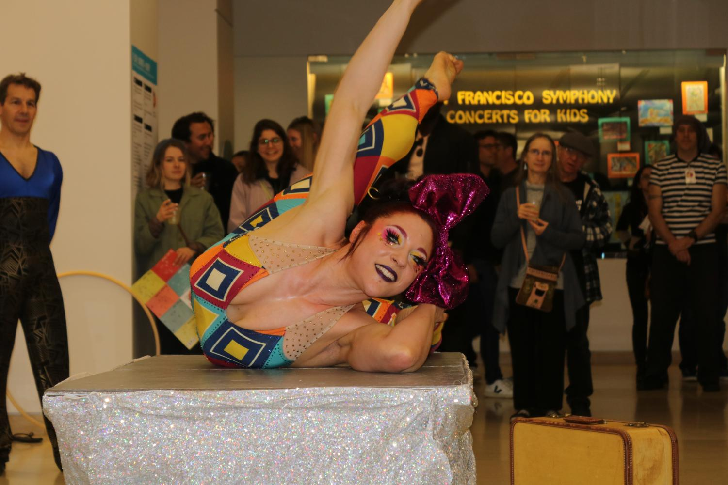 A vibrant contortionist positions herself elegantly as Night of Ideas attendees observe in awe.