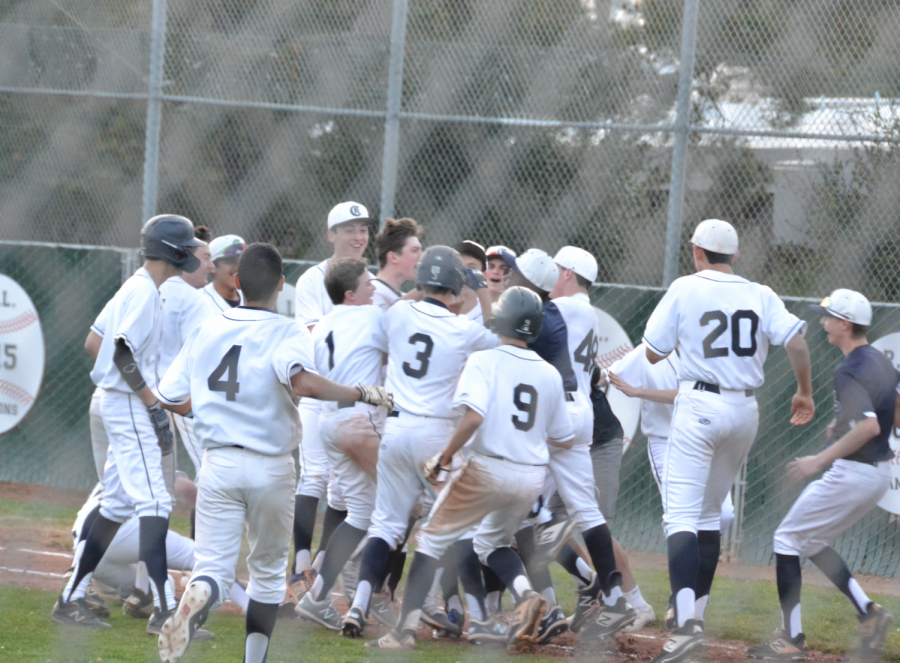 The team rushes to Brady Greene, a sophomore, after he delivered the game winning hit.