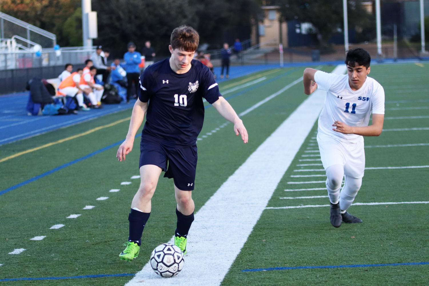 Dylan Roskind, a junior, dribbles the ball down the sideline and past a defender.