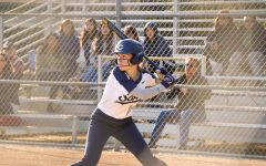 Alyse Murray, a junior and co-captain of the JV softball team, winds up to hit the ball.