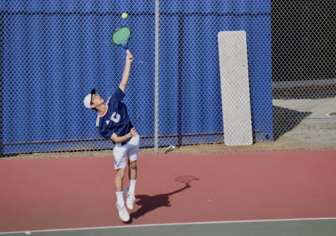 Kenny Lee, a junior, serves the ball across the court to his opponent.