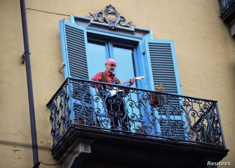 A man plays guitar as part of Italy's musical event organized to raise morale for COVID-19.