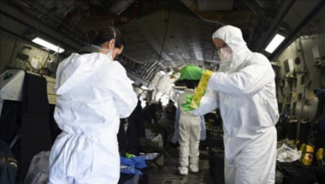 Airmen assist one another in donning their personal protective equipment, while on-board an Air Force C-17 Globemaster III during transportation isolation system training at Joint Base Charleston, South Carolina. Engineered and implemented after the Ebola virus outbreak in 2014, the TIS is an enclosure the Department of Defense can use to safely transport patients with diseases like novel coronavirus.