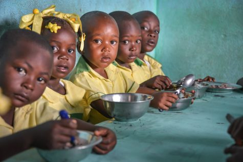 A group of malnourished children in Haiti eat a small meal together.