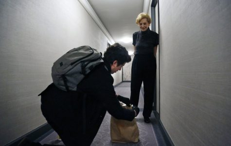 Liam Elkind, a co-founder of the Invisible Hands operation, delivers groceries for Carol Sterling.