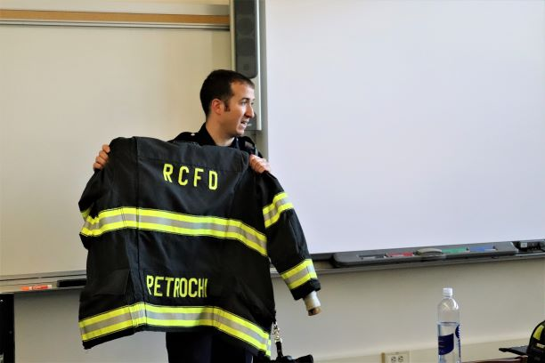 Petrochi shows his firefighter jacket to the attendees of the meeting.