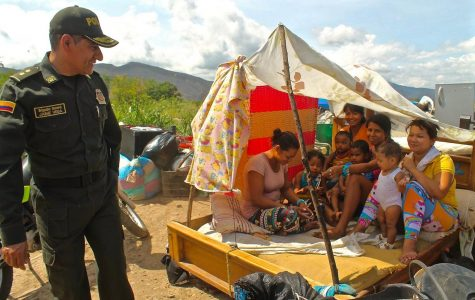 Police check on refugees as they embark on their journey to begin a new life.