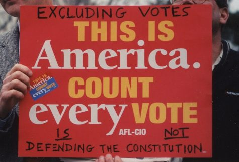 A person holds up a sign protesting the Electoral College system and the outcome of the 2000 election.