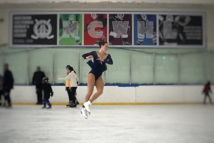 Joelle Faybishenko pulls her arms and legs in tightly to for an axel.