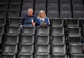A couple sits in dismay after the NBA cancels a contest between the Utah Jazz and Oklahoma City Thunder and announces an indefinite suspension of play.