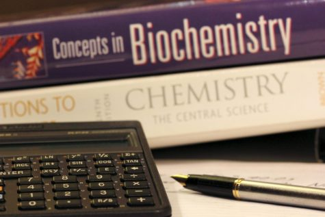 A calculator and several textbooks lay on a table.